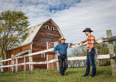 two farming caucasian cowboys standing by a wooden fence having a discussion in front of a red barn on a warm bright sunny day in summer.