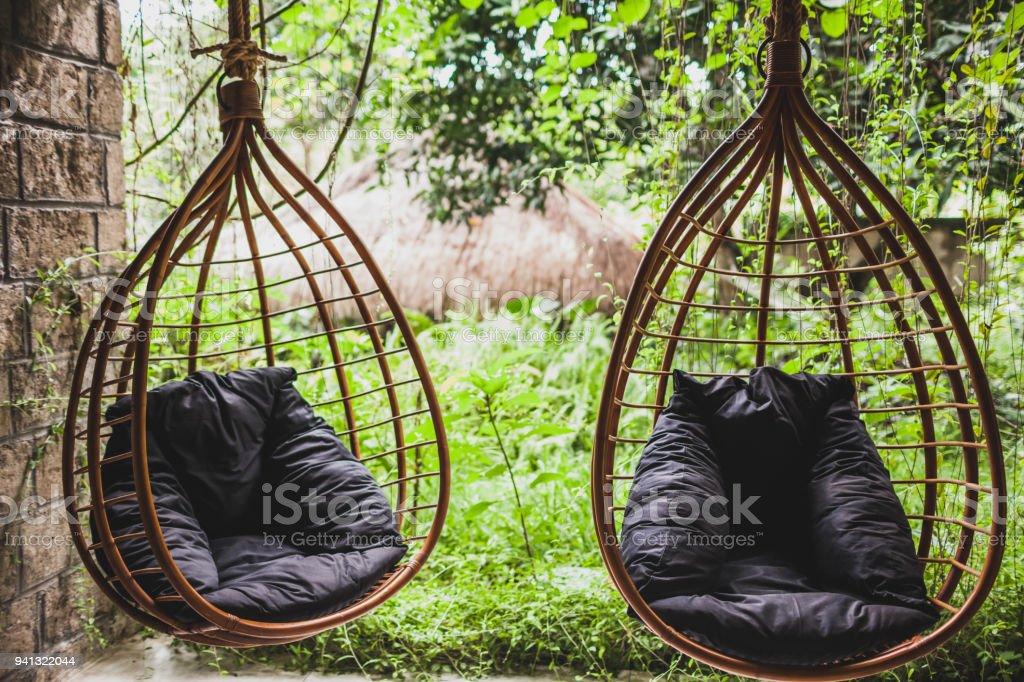 Zwei Rattan Korbsessel Mit Schwarzen Kissen Im Garten Im Sommer