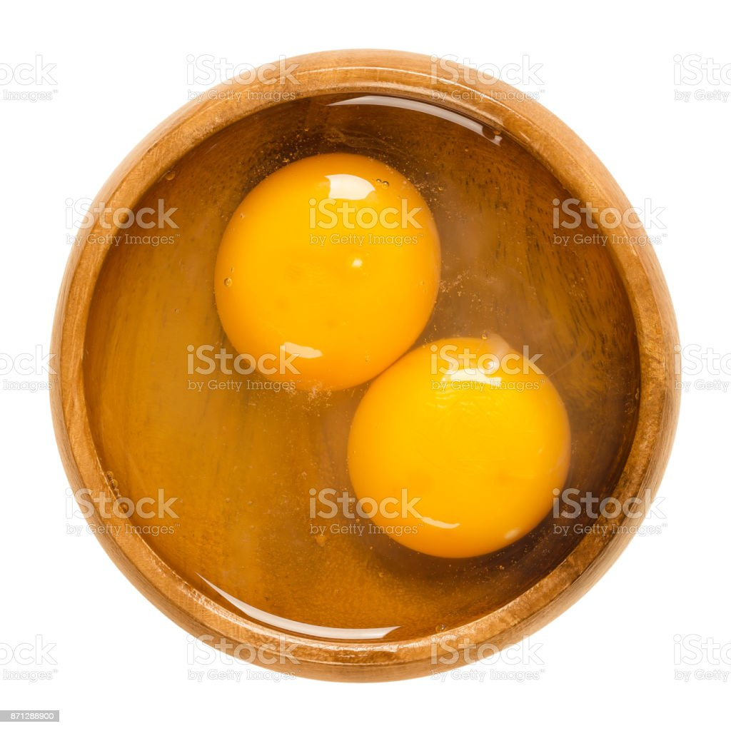 Two raw chicken eggs cracked into a wooden bowl stock photo