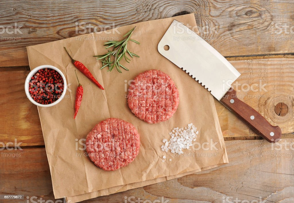 two raw patties of minced meat in the form of a circle and a knife machete to paper stock photo