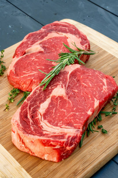 Two Raw Ribeye Steaks With Sprigs Of Rosemary And Thyme On A Wood Cutting Board stock photo