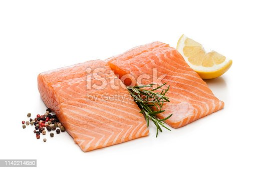 Two raw salmon fillets isolated on white background. Olive oil, lemon and pepper complete the composition. DSRL studio photo taken with Canon EOS 5D Mk II and Canon EF 100mm f/2.8L Macro IS USM.