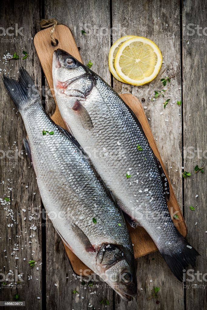 two raw seabass on cutting board with lemon stock photo
