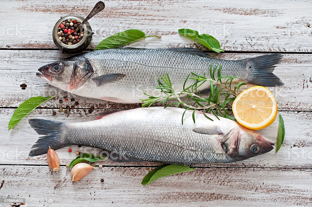 Two raw seabass with spices on an old wooden background. stock photo