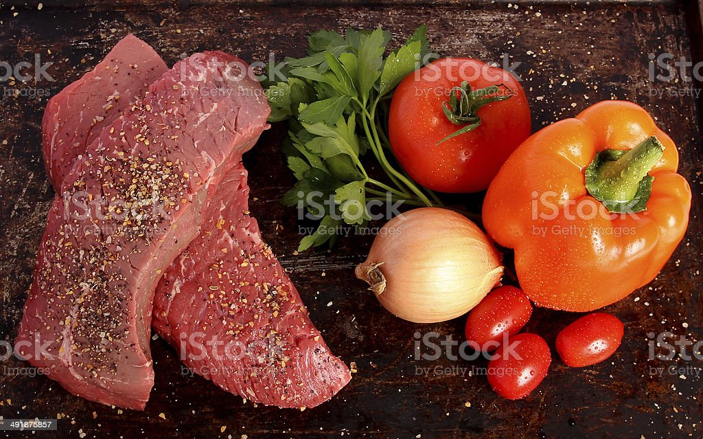 Two raw steaks with vegetables stock photo