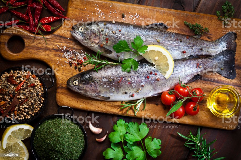 Two raw trout on dark slate background stock photo