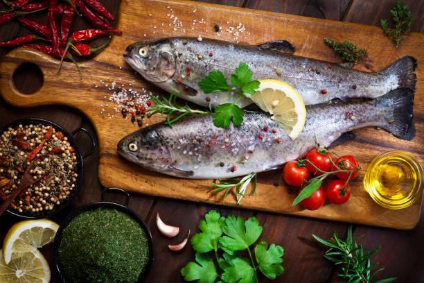 two raw trout on dark slate background - trout foto e immagini stock