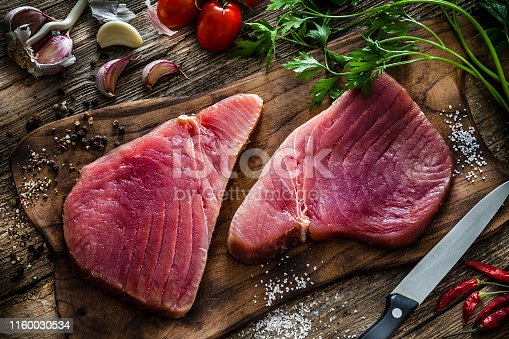 Raw food: top view of two fresh raw tuna steaks on a wooden cutting board shot on rustic wooden table. Some ingredients for cooking tuna steaks like, garlic, parsley, salt and pepper are all around the cutting board with the fillets. Predominant colors are red and brown. Low key DSRL studio photo taken with Canon EOS 5D Mk II and Canon EF 100mm f/2.8L Macro IS USM.