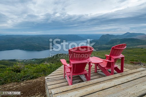458694311 istock photo Two Red Adirondack Chairs on Top of the Lookout Trail in Gros Morne 1174873938