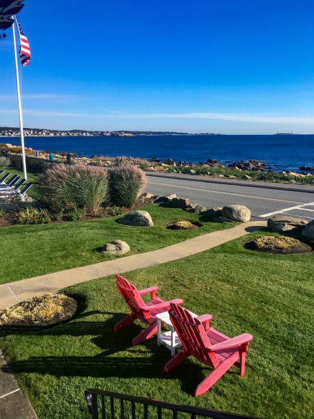 Two Red Adirondack Chairs Overlooking the Ocean in Gloucester, Mass New England Gloucester, MA / USA - Oct 19, 2018: Two red Adirondack chairs sitting on the grass overlooking the Atlantic Ocean on a beautiful, clear autumn day. Blue water and sky, American flag waving in the breeze. gloucester massachusetts stock pictures, royalty-free photos & images
