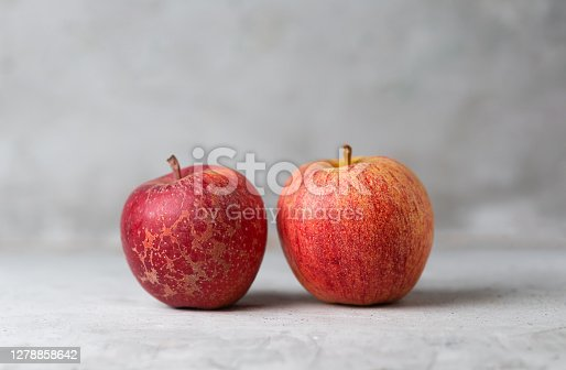 Two red apples on a green vertical background