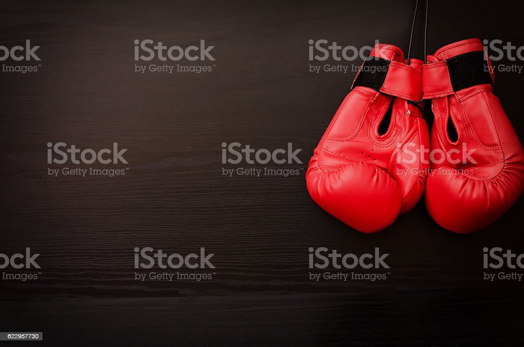 Two red boxing gloves hanging on a black background stock photo