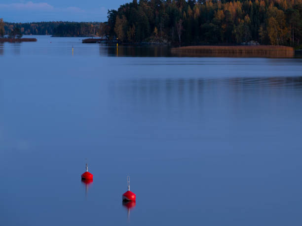 Two red buoys floating in calm sea on a beautiful autumn evening. stock photo