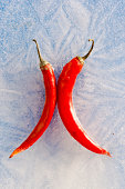 two red chilli peppers frozen in winter  ice
