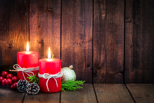 Two red Christmas candles with Christmas decoration on rustic wood table. The candles are at the left of an horizontal frame leaving useful copy space for text and/or logo at the right. Predominant colors are brown and red. DSRL studio photo taken with Canon EOS 5D Mk II and Canon EF 70-200mm f/2.8L IS II USM Telephoto Zoom Lens