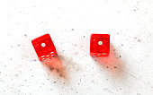 Two red craps dices showing Snake Eyes (double number one) overhead shot on white board