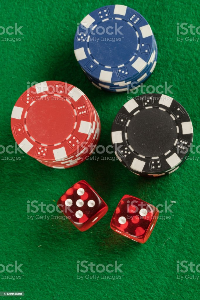 two red dices and different chips on green background. gambling and...