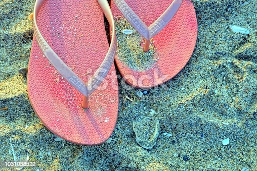 istock two red dirty plastic slippers in the sand on the beach 1031038522