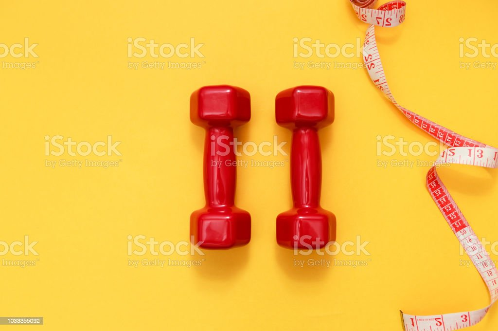 Two red dumbbells and tape measure. Fitness concept stock photo