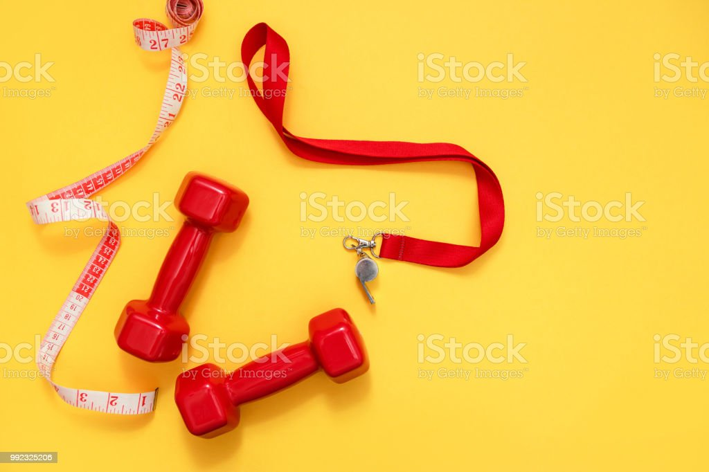 Two red dumbbells, tape measure and whistle stock photo