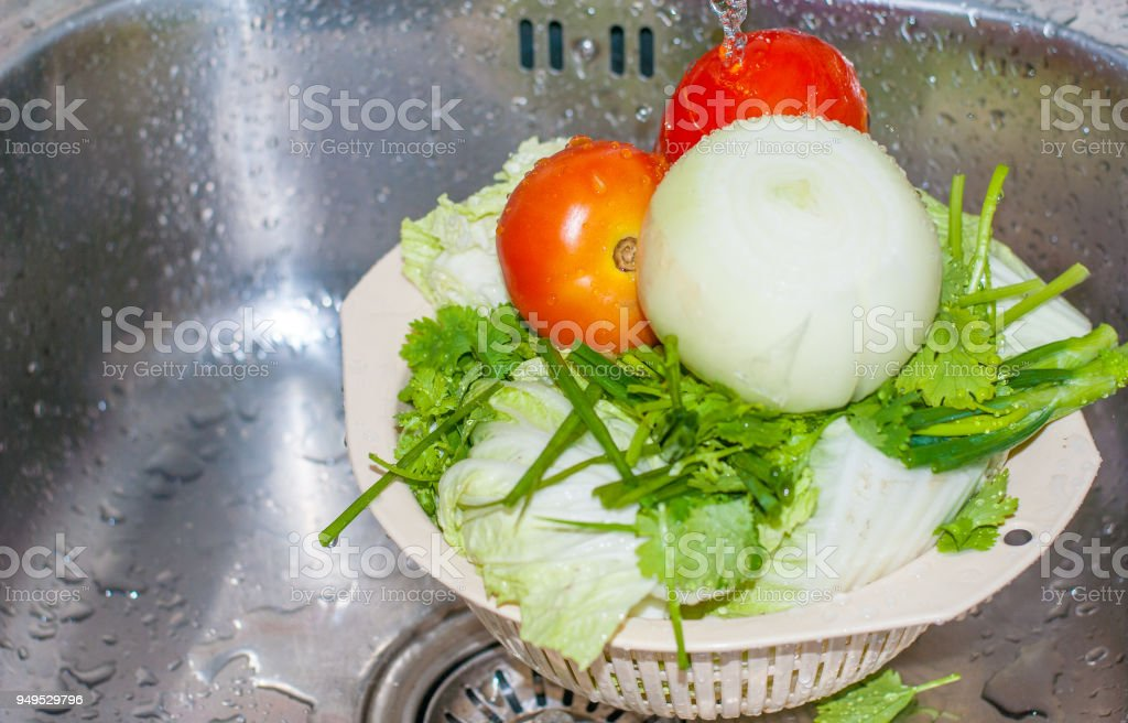 Two red fresh tomatoes , green pasley, big onion and cabbage are being cleaned  by water falling down from tab in silver kitchen sink, food ingredient preparation stock photo