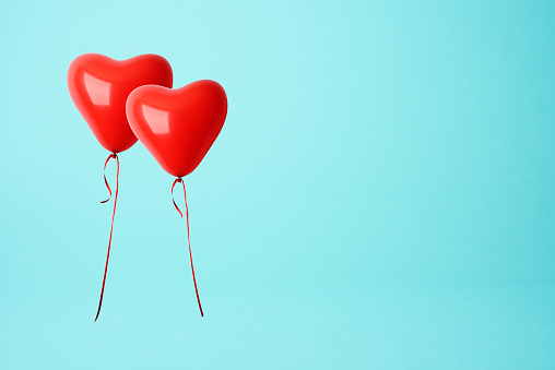 Two red heart shape balloons against blue background