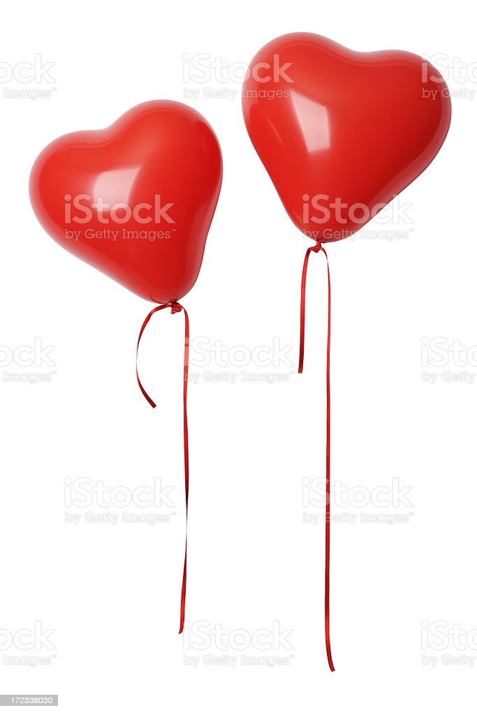 Two red heart shape balloons with ribbon against white background stock photo