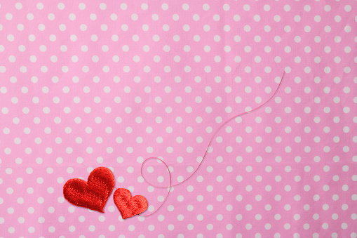 Over Head shot of two red heart shape embroidery with red thread on polka dot tablecloth.