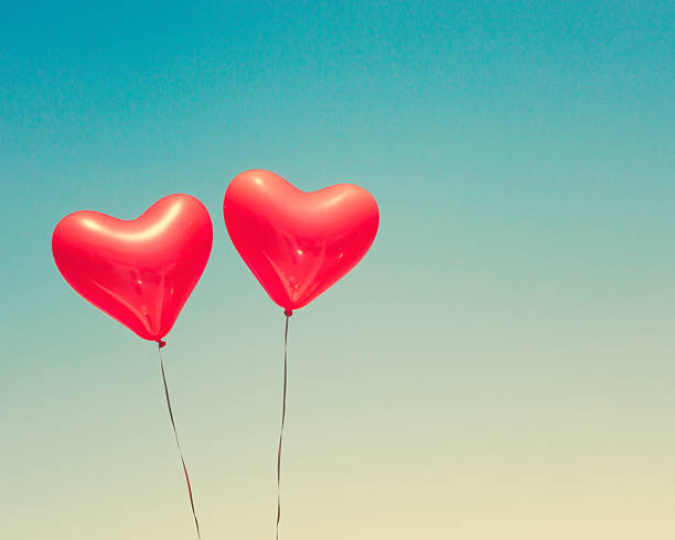 Two red heart shaped balloons stock photo