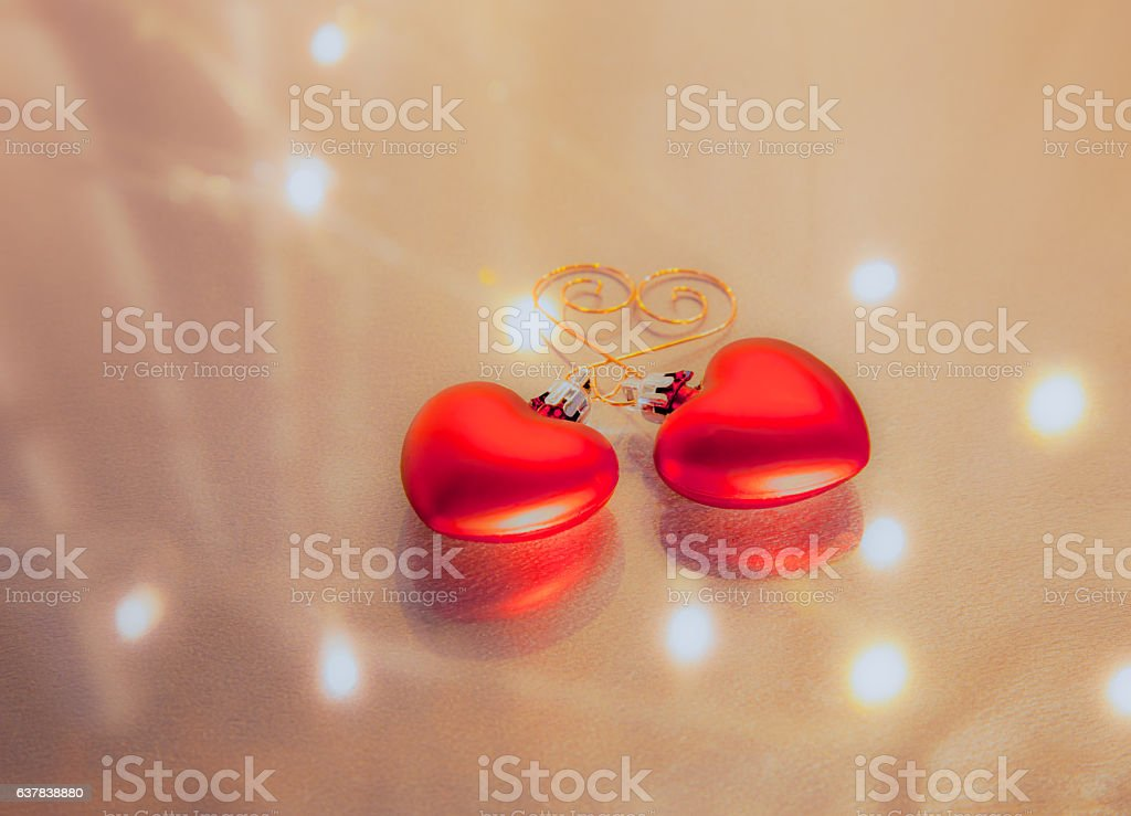 Two red hearts are hooked together and reflected (P) stock photo