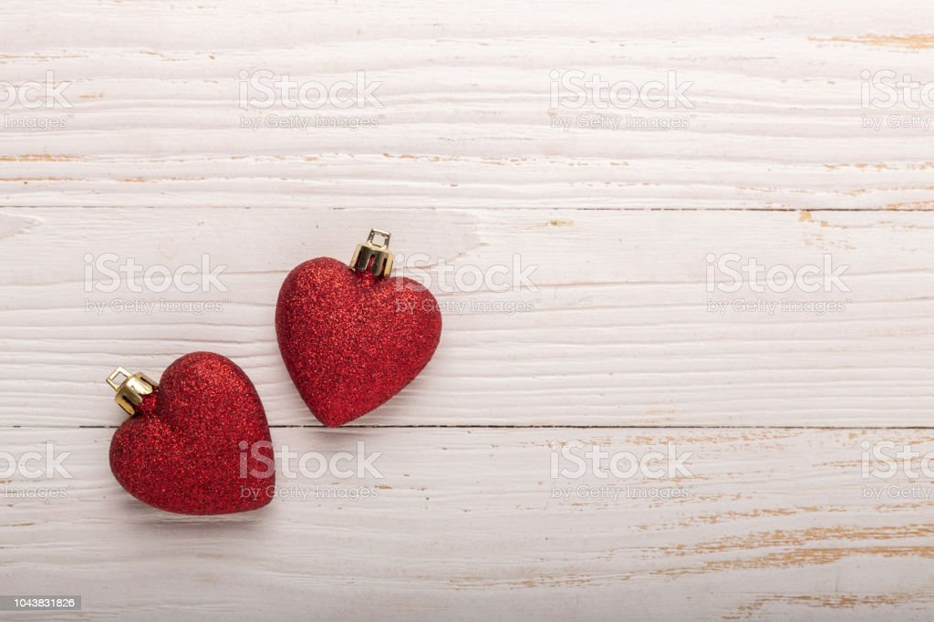 Two red hearts christmas gifts on white wooden background. Top view