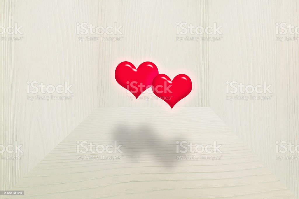 Two red hearts floating in vintage grey wooden room stock photo