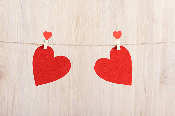 Two red hearts hung on the rope stock photo