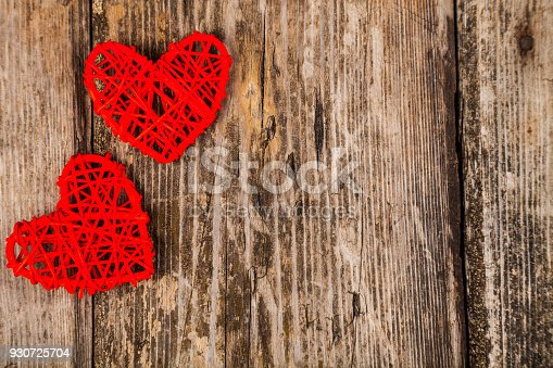 istock Two red hearts on an old wooden background 930725704
