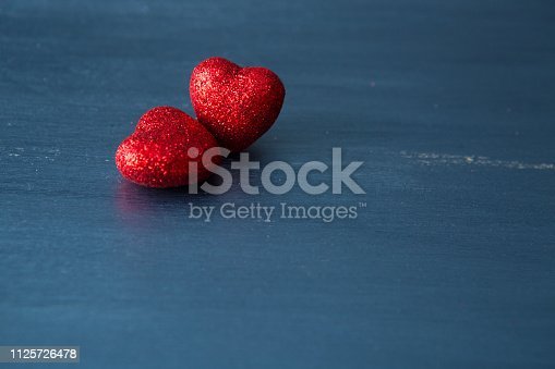 istock Two red hearts on dark blue or silver on wooden or metal background. Valentine's Day 1125726478
