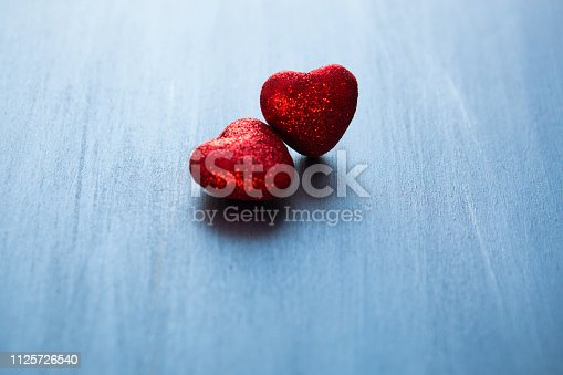 istock Two red hearts on dark blue or silver on wooden or metal background. Valentine's Day 1125726540