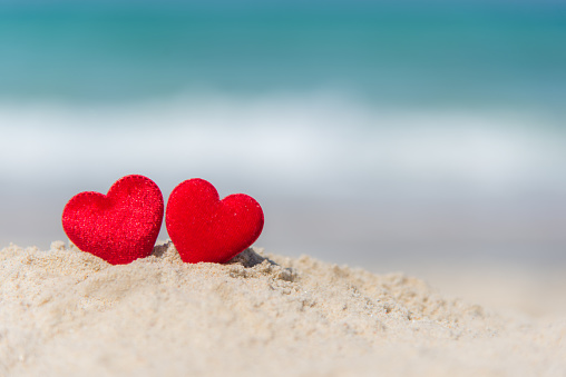 Two red hearts on the summer beach.  Valentine Day.