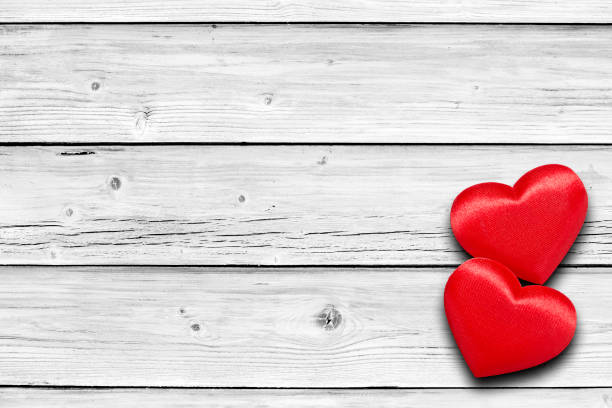 two red hearts on white weathered wooden table - i love you stock photos and pictures