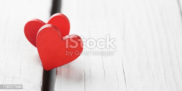 istock Two red hearts on wooden background, close-up 1192277550
