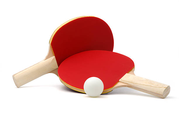 two red ping-pong paddles and white ball on white ground - paddle stockfoto's en -beelden