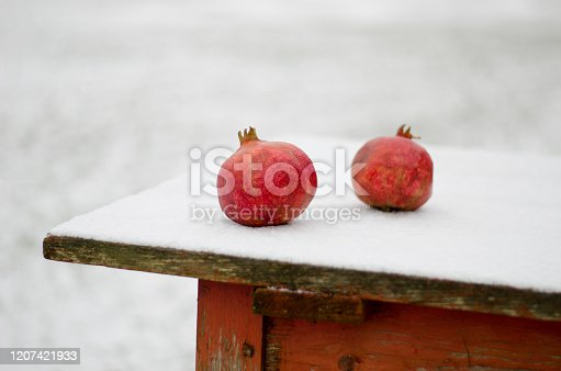 Two red pomegranate on snowy wooden table in winter time