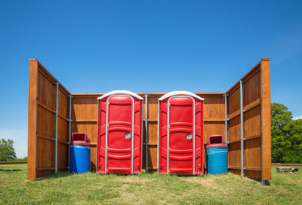 Two red portable restrooms with a wood fence around them in a park Two red portable restrooms and trash cans with a wood fence around them in a park. Trees and blue sky background. portable toilet stock pictures, royalty-free photos & images
