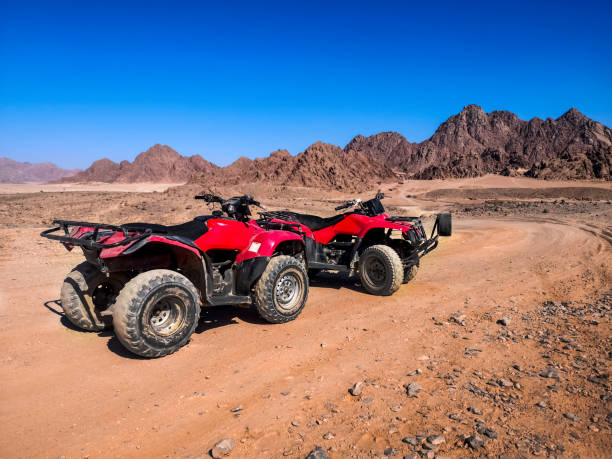 Two red quads stand near the mountains in the South Sinai desert near Sharm El Sheikh (Egypt) stock photo