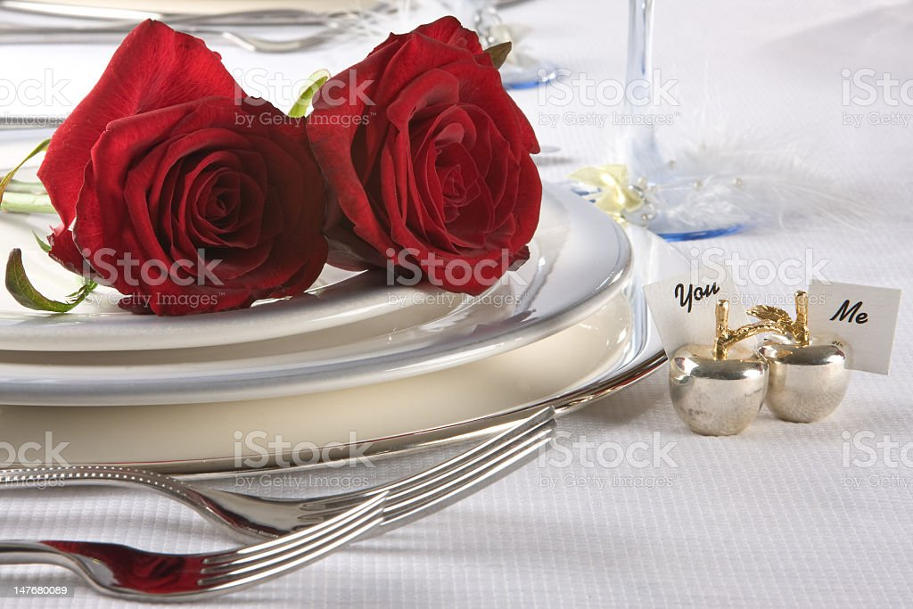 Two red roses lay on a white plate with You and Me placards stock photo