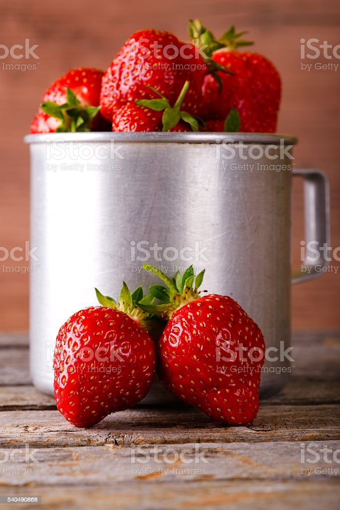 Two red strawberries in front of aluminum cup stock photo