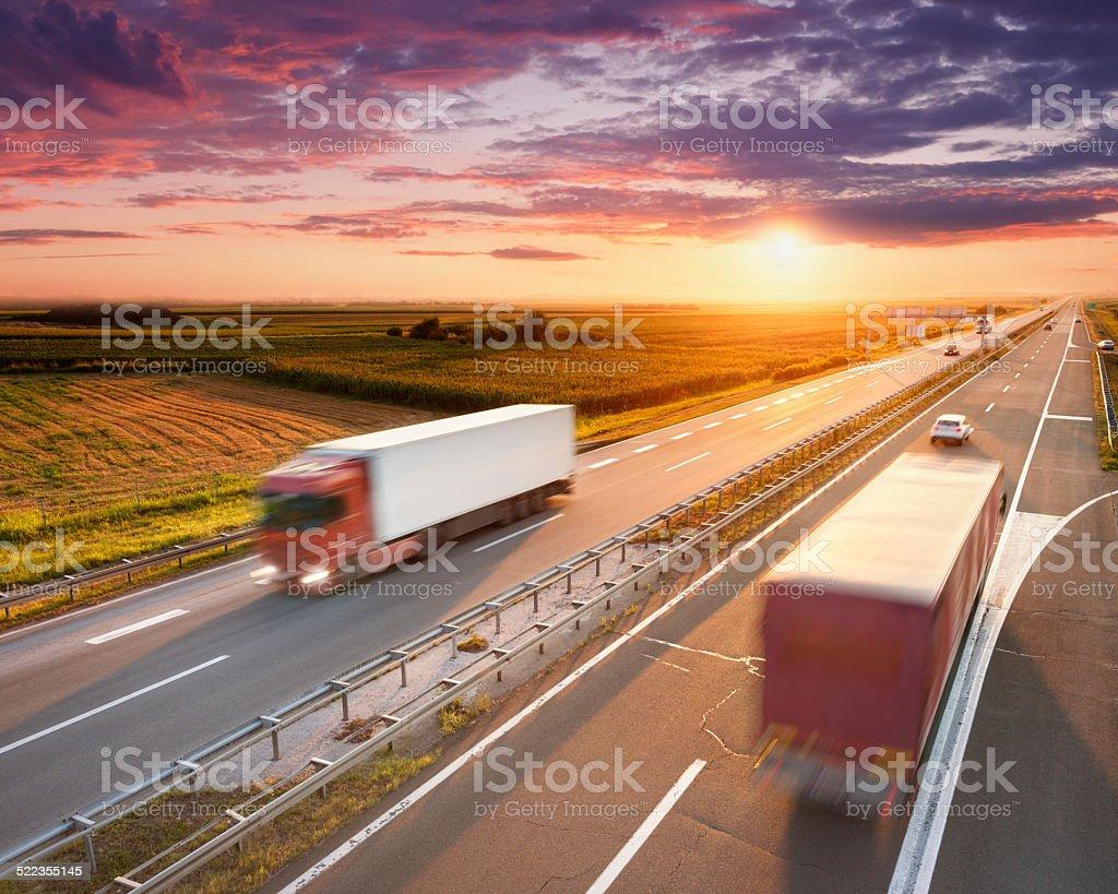 Dos camiones Rojo en la carretera al atardecer - foto de stock