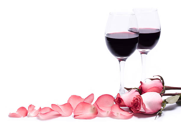 Two red wine glasses with pink rose petals stock photo