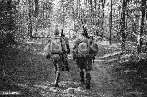 1143756392 istock photo Two Re-enactors Dressed As World War II Russian Soviet Red Army Soldiers Marching Through Forest. Photo In Black And White Colors. Soldier Of WWII WW2 Times 1143748870