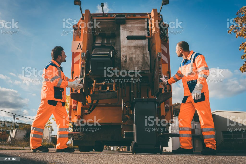 Two refuse collection workers loading garbage into waste truck stock photo