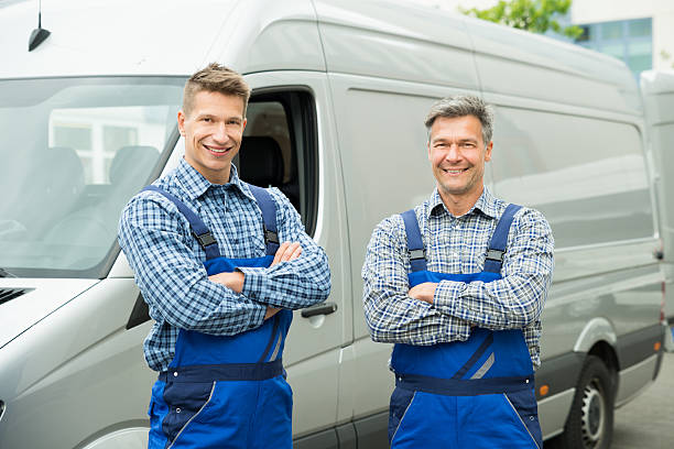 Two Repairmen With Arms Crossed In Front Of Van stock photo